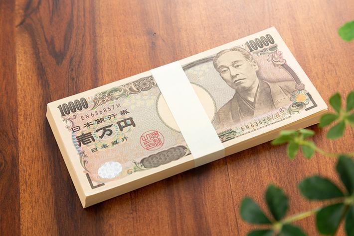 枝が映り込んでいるお金の写真