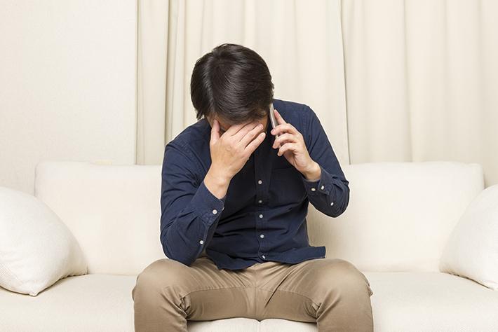 頭を抱えて電話をしている男性の写真