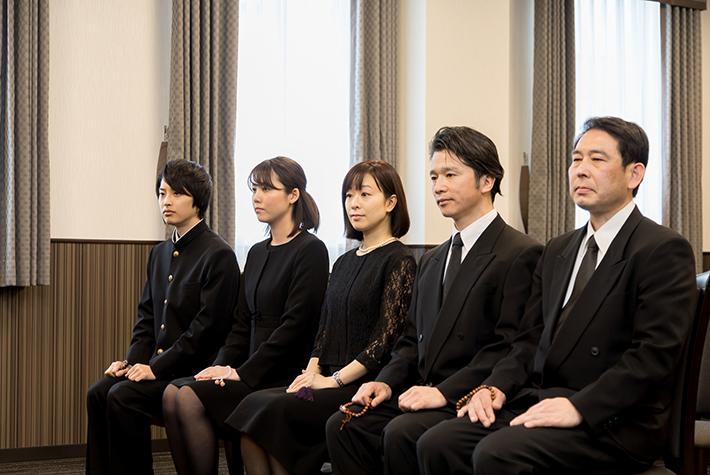 並んで座っている喪服姿の人の写真